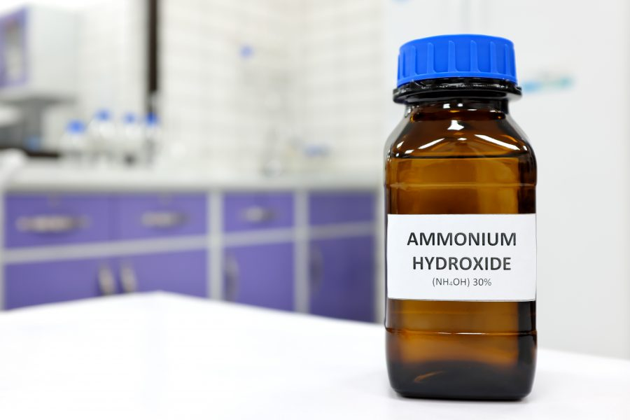 Brown glass bottle of ammonium hydroxide in lab setting