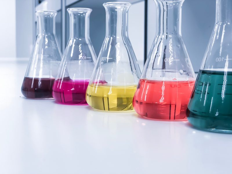 5 Erlenmeyer flasks lined up on laboratory desk, each with different coloured solutions inside